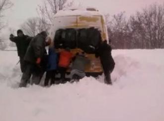 Elevi, nevoiți să deblocheze autobuzul care a rămas blocat în nămeți